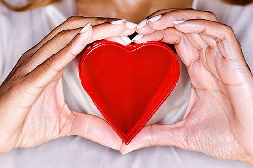 بنت تمسك قلب أحمر جميل