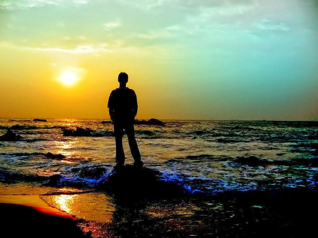 شاب حزين يقف في مياه البحر مهموما.