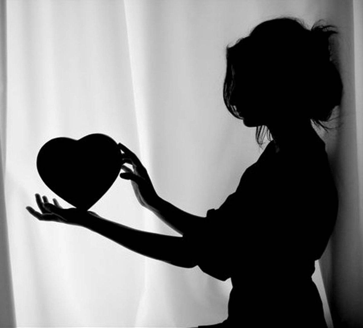 فتاة تمسك بقلب بين يديها.